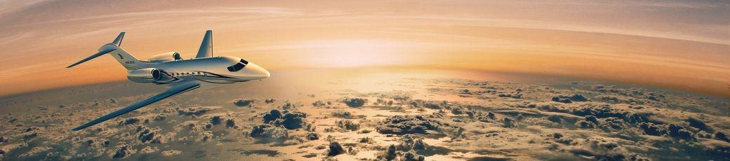 Privatjet im Flug mit Sonnenaufgang im Hintergrund